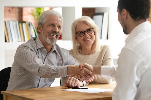Happy old couple clients make financial deal handshake meeting lawyer